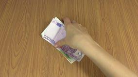 A mão do homem dá o grupo do euro- subôrno das cédulas do dinheiro para a mulher 4K vídeos de arquivo