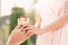 A mão do homem dá uma caixa de presente pequena à mulher Foto de Stock