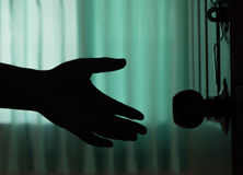 A mão do homem da sombra abre a porta Foto de Stock