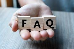 A mão do homem de negócio que guarda o cubo de madeira com texto do FAQ fez frequentemente perguntas no fundo da tabela Financeir foto de stock royalty free