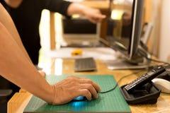 Mão do homem de negócio que guarda o rato com o colega que olha o comput imagem de stock