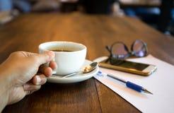 Mão do homem de negócio que guarda a xícara de café com pena e telefone celular imagem de stock royalty free