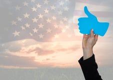 Mão do homem de negócio que mantém um polegar acima contra a bandeira americana fotografia de stock