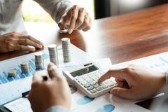 Mão do homem de negócio que põe a pilha da moeda para o investimento do dinheiro da economia do orçamento e a gestão explicando f fotografia de stock royalty free