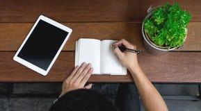 a mão do homem de negócio usando o portátil e escreve a nota inspira a ideia na madeira Imagens de Stock