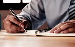 A mão do homem de negócios é de assinatura ou redigindo documentos fotos de stock royalty free