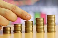 A mão do homem de negócios é moeda de ouro da pilha do concep crescido financeiro imagem de stock