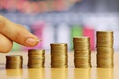 A mão do homem de negócios é moeda de ouro da pilha do concep crescido financeiro fotos de stock royalty free