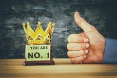 Mão do homem de negócios ao lado do troféu da concessão para a vitória da mostra ou o primeiro lugar de vencimento fotografia de stock royalty free