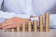 A mão do homem de negócios atrás das moedas do Euro na mesa Imagens de Stock Royalty Free