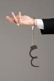 Mão do homem de negócios com algemas abertas Fotos de Stock Royalty Free
