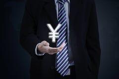 Mão do homem de negócios com sinal de moeda dos ienes Fotos de Stock