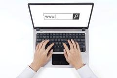 A mão do homem de negócios datilografa o texto de WWW no portátil foto de stock