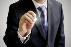 A mão do homem de negócios escreve no ar Imagens de Stock