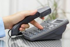 A mão do homem de negócios está discando um número de telefone com headse pegarado Imagens de Stock Royalty Free