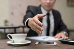 A mão do homem de negócios estendeu-o ao aperto de mão na cafetaria imagem de stock