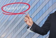 A mão do homem de negócios novo escreve a ação de graças da palavra no skyscra Fotos de Stock