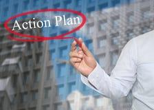 A mão do homem de negócios novo redige o plano de ação da palavra no skyscrap Imagem de Stock Royalty Free