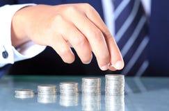 A mão do homem de negócios põr moedas Imagem de Stock Royalty Free