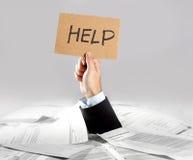 Mão do homem de negócios que emerge da mensagem carregada da ajuda da terra arrendada da mesa do documento Foto de Stock