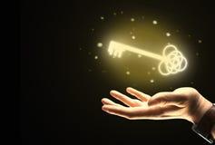Mão do homem de negócios que guarda a chave dourada Imagens de Stock