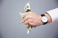 Mão do homem de negócios que guarda contas do dólar americano no punho Fotos de Stock Royalty Free