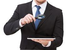 Mão do homem de negócios que guarda a lente de aumento sobre o PC da tabuleta Fotografia de Stock