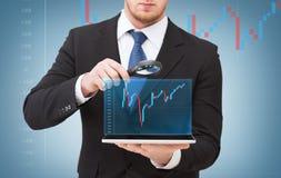Mão do homem de negócios que guarda a lente de aumento sobre o PC da tabuleta Imagens de Stock