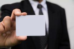Mão do homem de negócios que guarda o cartão branco no branco Fotos de Stock
