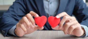 Mão do homem de negócios que guarda o coração do vermelho dos pares imagens de stock
