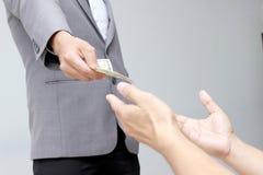 Mão do homem de negócios que guarda o dólar americano, USD as contas, dinheiro da cédula do dólar das ofertas e dinheiro da doaçã Imagem de Stock