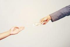 Mão do homem de negócios que guarda o dólar americano, USD as contas, dinheiro da cédula do dólar das ofertas e dinheiro da doaçã Imagens de Stock Royalty Free