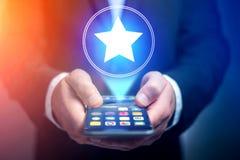 Mão do homem de negócios que guarda o telefone celular com ícone favorito da estrela foto de stock