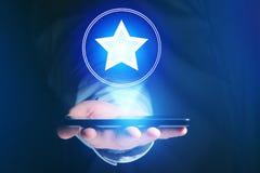 Mão do homem de negócios que guarda o telefone celular com ícone favorito da estrela fotografia de stock