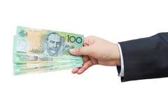 Mão do homem de negócios que guarda os dólares australianos (AUD) no fundo isolado Imagens de Stock