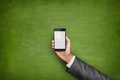 Mão do homem de negócios que guarda a parte dianteira do smartphone de Foto de Stock Royalty Free
