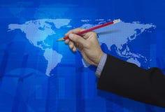 Mão do homem de negócios que guarda um lápis sobre vagabundos digitais azuis do mapa do mundo Fotografia de Stock