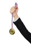 Mão do homem de negócios que guarda um MEDA do ouro imagem de stock