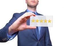 Mão do homem de negócios que mantém cinco estrelas isoladas no fundo branco Fotos de Stock