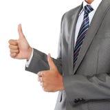 A mão do homem de negócios que mostra os polegares levanta o sinal Imagens de Stock