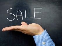 Mão do homem de negócios que mostra quadro escrito à mão do quadro-negro do texto da venda Fotografia de Stock Royalty Free