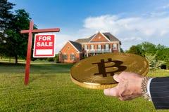 Mão do homem de negócios que oferece Bitcoin comprar a casa Fotografia de Stock