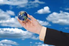 Mão do homem de negócios que prende um globo Fotografia de Stock Royalty Free