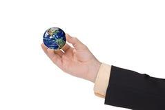 Mão do homem de negócios que prende um globo Fotografia de Stock