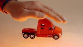 A mão do homem de negócios que protege o caminhão vermelho do brinquedo no seguro de carro reflexivo da mesa video estoque
