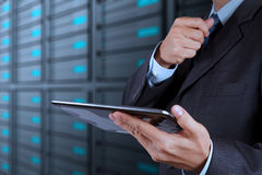 Mão do homem de negócios usando a sala do tablet pc e do servidor