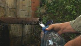 A mão do homem derrama a água de mola natural na garrafa filme
