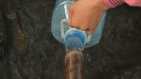 A mão do homem derrama a água de mola natural na garrafa video estoque