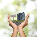 Mão do homem e do gramado verde com condomínio e sinais de madeira Fotografia de Stock Royalty Free