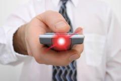 Mão do homem em um de controle remoto com a luz que irradia-se do telecontrole fotos de stock